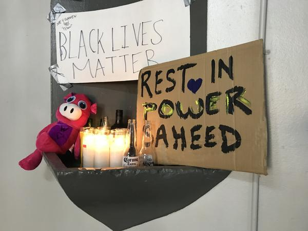 A makeshift memorial for Saheed Vassell, 34, stands Thursday in the lobby of the apartment building that neighbors identified as his father's residence.