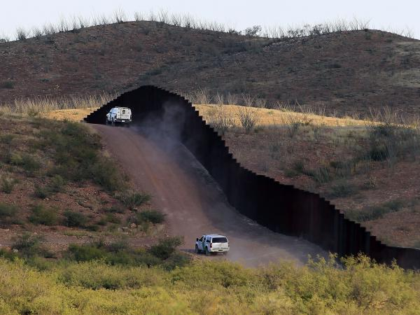U.S. Border Patrol agents patrol the border fence in Naco, Ariz. President Trump wants to send National Guard contingents to assist them.