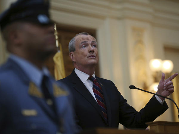 As a New Jersey state trooper stands guard nearby, Gov. Phil Murphy unveils his 2019 budget. In April, Murphy signed an order making gun violence data more accessible. (AP Photo/Mel Evans)