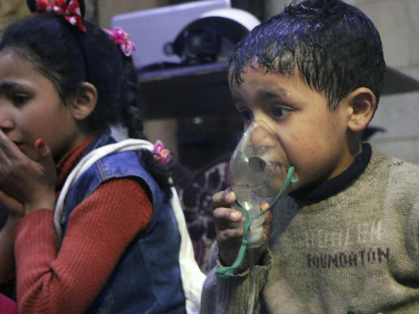 This image released early Sunday by the Syrian Civil Defense White Helmets shows a child receiving oxygen through respirators following an alleged poison gas attack in the rebel-held town of Douma, near Damascus, Syria.