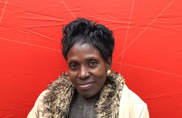 """Consolata Aganga goes door-to-door as a community health worker, a demanding volunteer job. """"It is God who gives me the strength,"""" she says. She is also a small-scale farmer, growing vegetables for her family."""