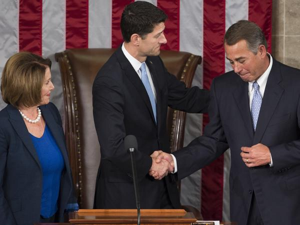 In 2015, newly elected Speaker of the House Paul Ryan shakes hands with outgoing Speaker John Boehner alongside House Democratic leader Nancy Pelosi at the U.S. Capitol.
