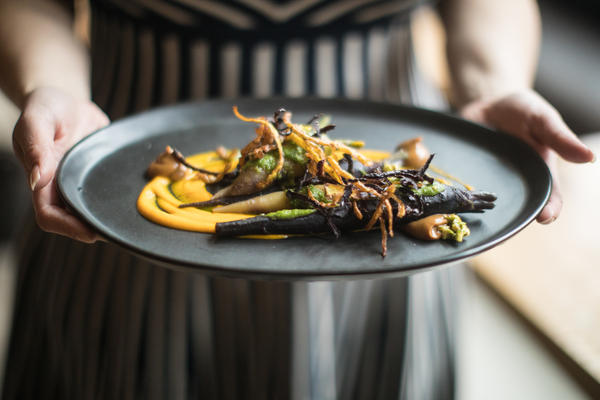 """This dish is every form of carrot you can use,"" Ma says. It features blanched, sauteed heirloom carrots topped with fried, crunchy strips of carrot skin with a side of pesto made with pureed carrots and the green carrot tops that are usually discarded."
