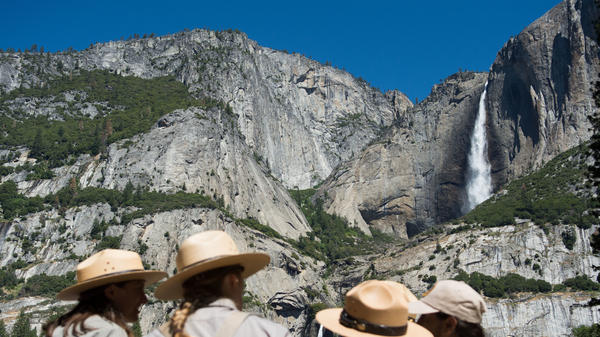 Park rangers meet in front of Yosemite Falls in 2016 in Yosemite National Park in California. Increased fees are expected to boost funding for park maintenance across the country.