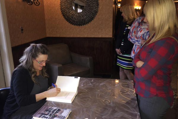 Sdoia signs a copy of her book <em>Perfect Strangers.</em>