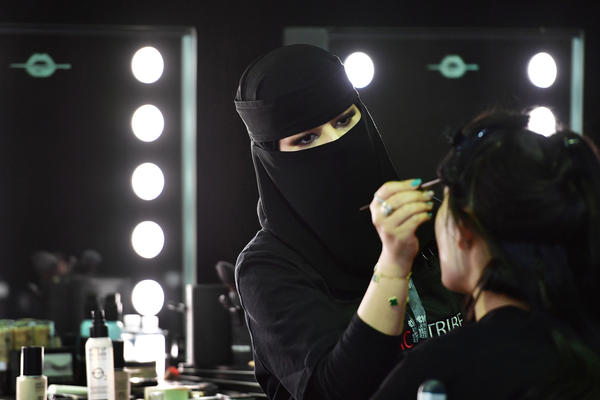 A Saudi makeup artist preps a model backstage during Saudi Arabia's first Arab Fashion Week in Riyadh.