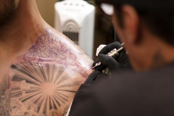 Freddy Negrete, 61, works on a tattoo on a customer's shoulder.