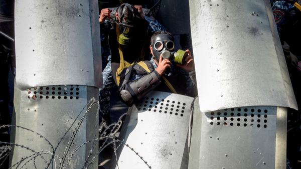 """Armenian special police hunker down behind a barbed wire barrier in central Yerevan on Monday. According to <a href=""""https://www.hrw.org/news/2018/04/16/protests-surge-armenia"""">some witnesses</a>, used stun grenades against the protesters who sought to break through the barrier that blocked them from the parliament building."""