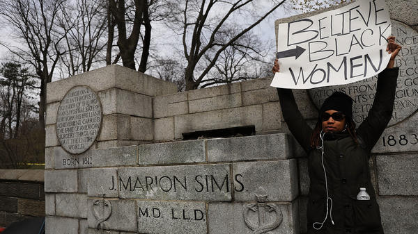 "A woman stands beside the empty pedestal where a statue of J. Marion Sims used to stand. Multiple groups demanded the removal of the statue, which sat on a pedestal praising his achievements as ""brilliant"" without acknowledging the women who endured his painful experiments."
