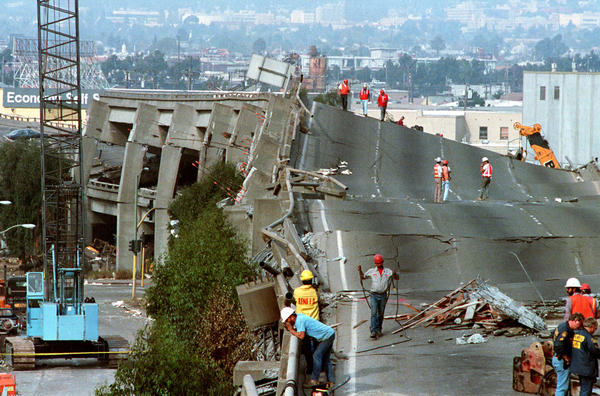 FILE - In this Oct. 19, 1989 file photo, workers check the damage to Interstate 880 in Oakland, Calif., after it collapsed during the Loma Prieta earthquake two days earlier that killed 63 people, injured almost 3,800 and caused up to $10 billion damage. (Paul Sakuma/AP)