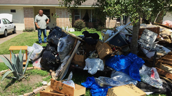 Salvador Cortez surveys debris in his front yard in Houston after Hurricane Harvey last year.