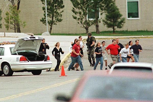 Students run from Columbine High School on April 20, 1999.