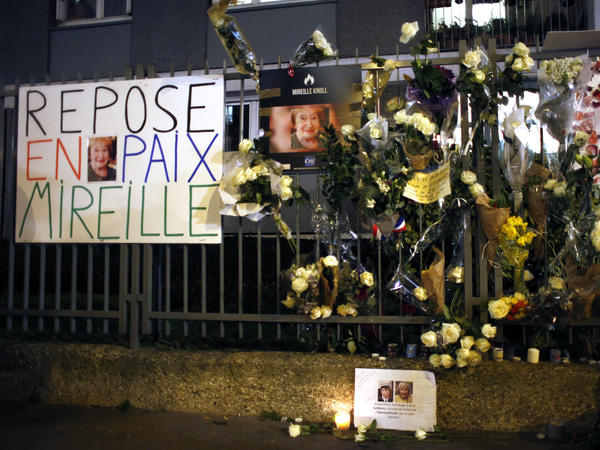 Flowers and placards are displayed outside Knoll's apartment in Paris in March. Knoll's death has taken on national importance.