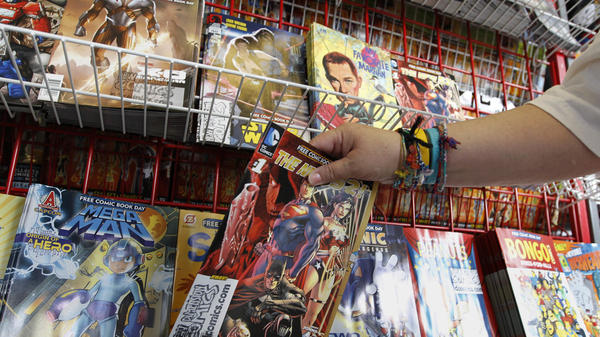 Mary Ann Shilts takes one of the free comic books from the display rack at the New Dimensions Comics store in Cranberry, Pa. during Free Comic Book Day 2012.