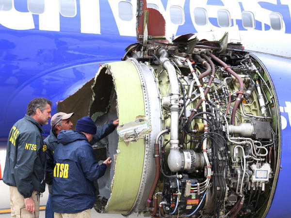 National Transportation Safety Board investigators examine damage to the engine of the Southwest Airlines plane that made an emergency landing at Philadelphia International Airport in Philadelphia on Tuesday.