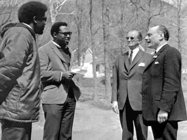 """Britain's Conservative Party politician Enoch Powell, right, listens to two demonstrators in Canada in April 1968, reading a petition that describes him as a """"racist."""""""