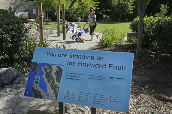 A sign notifies people they are standing on the Hayward Fault in the children's zoo area of the Oakland Zoo in Oakland, Calif.