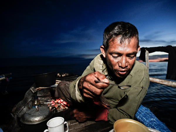 Amja Kasim Derise cooks dinner  on his boat in Sulawesi, Indonesia. The back of the boat is used for cooking, the middle for sleeping and the front for fishing.