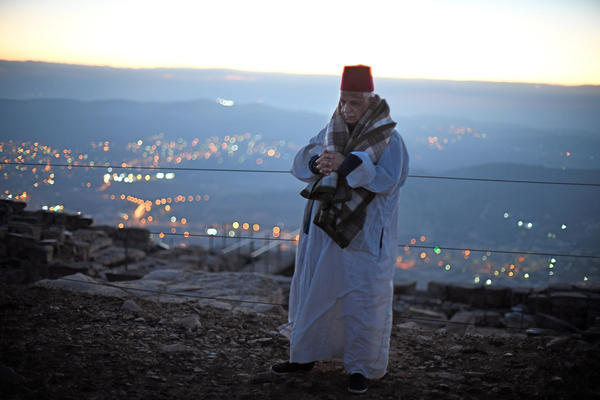 Tsedaka walks at the top of Mount Gerizim just before sunrise. He confirmed that the single leaf in Israeli army possession from an old Samaritan scroll is likely part of the missing Torah. The scroll is being sold piecemeal, its parchment leaves separated at the seams.