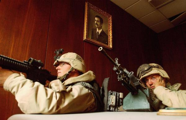 U.S. soldiers take cover near a portrait of Saddam Hussein while conducting a sweep of the VIP terminal of Baghdad International Airport on April 4, 2003.
