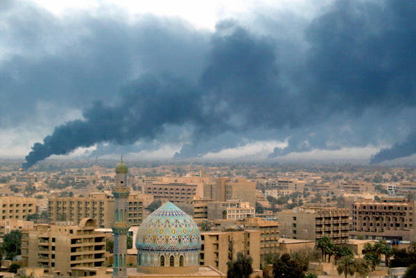 Smoke billowing from burning oil trenches covers Baghdad on April 2, 2003.