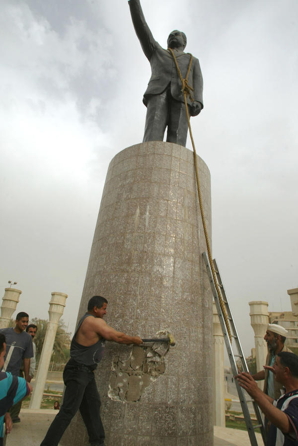 """Now, I really regret hitting the statue,"" says Qatham Sherif al-Jabouri, shown here on April 9, 2003, helping to topple a Saddam Hussein statue in Baghdad."