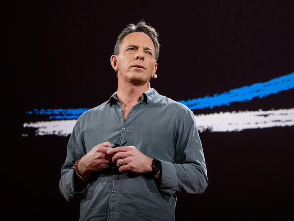 Dan Pallotta speaks on the TED stage.