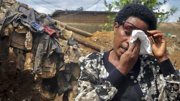 France Mukantagazwa, who lost her father and other relatives in the Rwanda genocide and believes their bodies may be in the newly found graves, cries as she speaks to reporters at the site on Thursday.