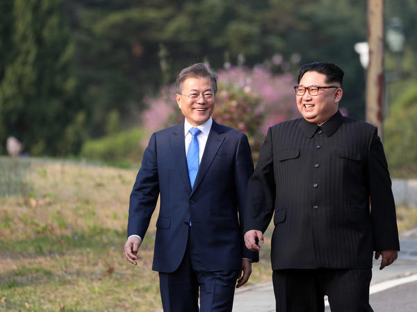Moon and Kim walk together after a tree-planting ceremony at the truce village of Panmunjom on Friday.