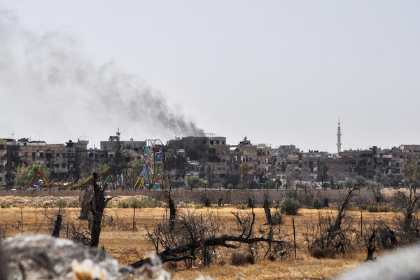 A picture taken during a Syrian army-organized tour on April 20 shows a view of Douma, on the outskirts of the capital Damascus, with a smoke plume rising in the background.