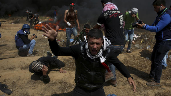 Palestinian protesters fall amid the billowing tear gas fired by Israeli troops along the Gaza-Israel border. Palestinians converged on the area for a new round of protests Friday.