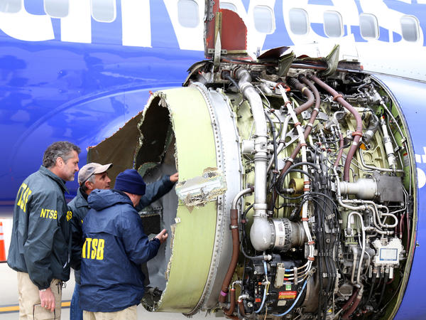 National Transportation Safety Board investigators examine damage to Southwest Airlines Flight 1380, which left one passenger dead and other injured on April 17. A passenger filed a lawsuit against the airline on Thursday.