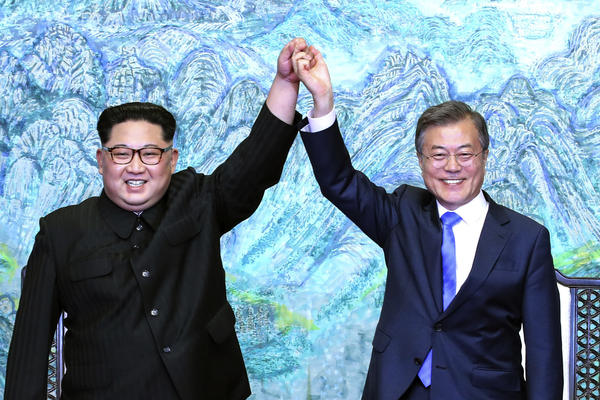 North Korean leader Kim Jong Un, left, and South Korean President Moon Jae-in raise their hands after signing a joint statement at the border village of Panmunjom.