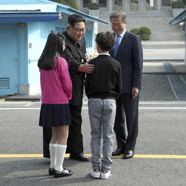 North Korean leader Kim Jong Un, left, and South Korean President Moon Jae-in, right, are greeted by children at the border.