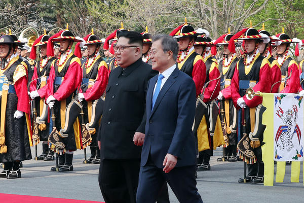 Kim and Moon walk to the official welcome hall after crossing the military demarcation line.