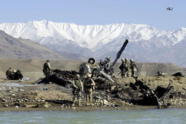 U.S. Army soldiers inspect the wreckage of a U.S. MH-53 Pave Low helicopter near Bagram Airfield on Nov. 24, 2003. Five soldiers were killed and seven others injured when the transport helicopter crashed while taking part in Operation Mountain Resolve, an operation to hunt down Taliban supporters and other militants.