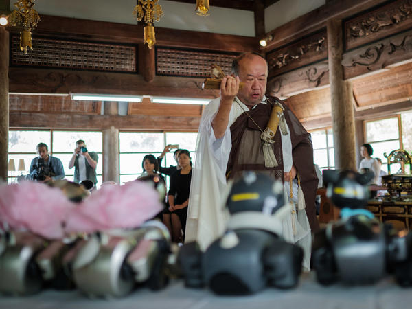 Kofukuji temple chief priest Bungen Oi with Aibos displayed on an altar at the Kofukuji temple in Isumi, Chiba, last week.