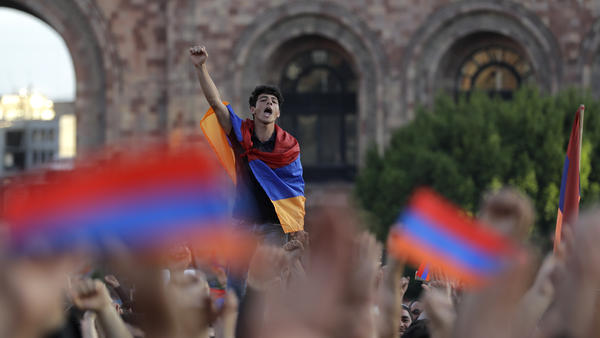 A demonstrator drapes himself in the Armenian flag at a rally supporting Nikol Pashinyan on Wednesday. He was just one of tens of thousands who packed Republic Square in the capital, Yerevan, and blocked roads and interrupted railway service.