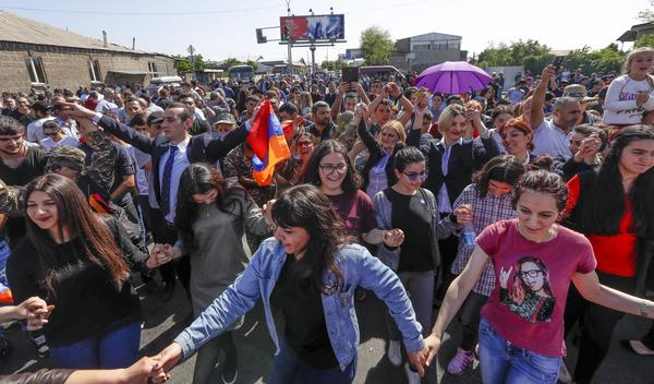 Pashinyan's supporters dance and sing as they block a road to the airport just outside Yerevan on Wednesday.