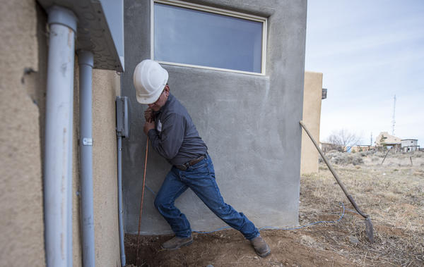 Kit Carson Co-Op installer technician Sidney Trujillo installs a box with fiber-optic wire onto a home in Taos.