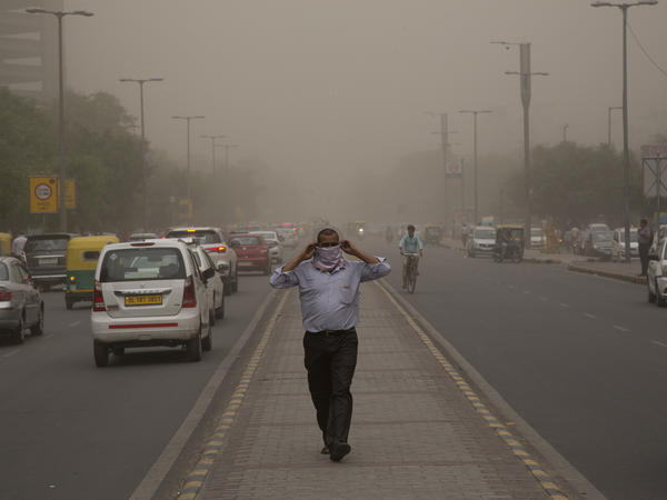 A man wraps a scarf around his nose as a dust storm envelops the city in New Delhi on Wednesday.