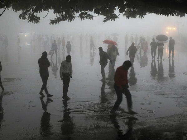 People walking under heavy rainfall in the northern hill town of Shimla in Himachal Pradesh state. Indian officials on Thursday said dozens had been killed and injured in the freak storm.