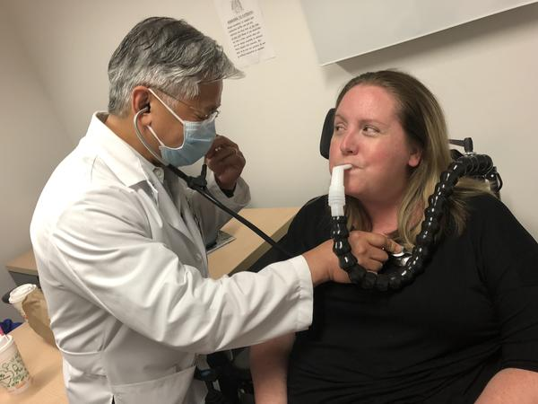 Dr. Tuan Vu with the University of South Florida ALS Clinic, checks 38-year-old Leigh Hotle for congestion.