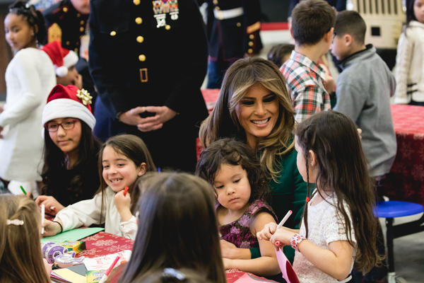 First Lady Melania Trump sits with 3-year-old Mehreem Donahue in her lap, as she makes Christmas cards with military kids, at the Marine Corps' annual Toys for Tots event on December 13th, 2017.