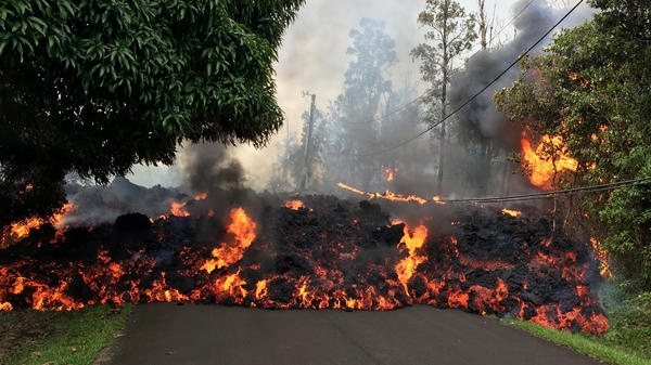 A lava flow moves on Makamae Street in the Leilani Estates subdivision on Sunday, following an eruption by Hawaii's Kilauea volcano. The governor of Hawaii has declared a local state of emergency and some 1,700 residents have been ordered to flee.