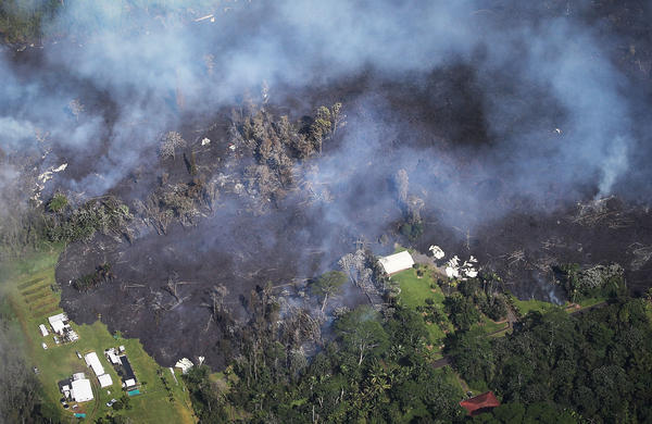 Lava from volcanic fissures slowly advances and overtakes structures and trees in the Leilani Estates neighborhood on Sunday. At least 26 homes have been destroyed by lava.