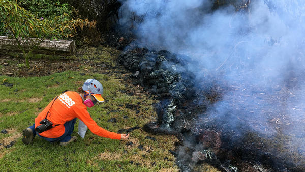 A Hawaiian Volcano Observatory geologist collects samples of spatter for laboratory analysis on Sunday in the Leilani Estates subdivision near Pahoa.