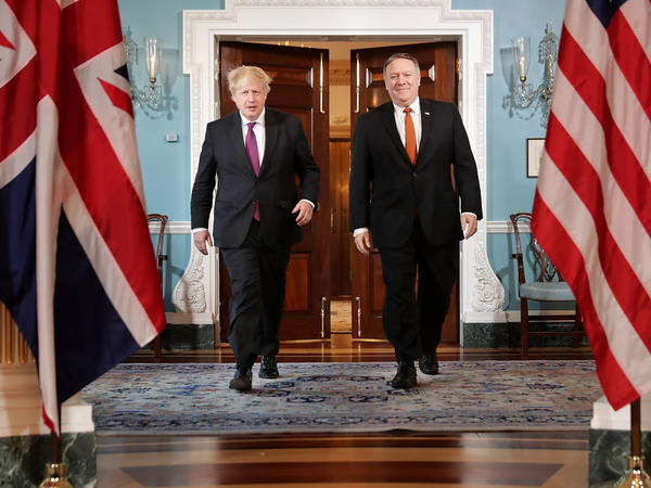 """British Foreign Secretary Boris Johnson (left) meets with Secretary of State Mike Pompeo at the State Department Monday. Johnson argued for the Trump administration to continue to be a party to the 2015 Iran nuclear deal. """"The wisest course would be to improve the handcuffs rather than break them,"""" Johnson wrote in the <em>New York Times.</em>"""