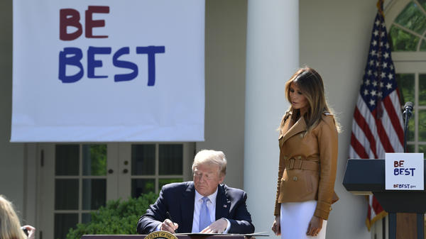 President Donald Trump signs a proclamation as first lady Melania Trump watches during an event where the first lady announced her initiatives in the Rose Garden of the White House Monday.