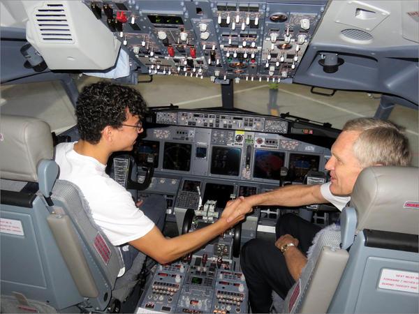 Instructor pilot Bob Hoelzen congratulates Sumner High School student Alexej Latimer for landing a Boeing 737 in a simulator during Alaska Airlines' annual Aviation Day.